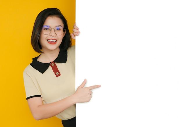 Retrato de menina bonita, apontando para o quadro branco com espaço vazio.