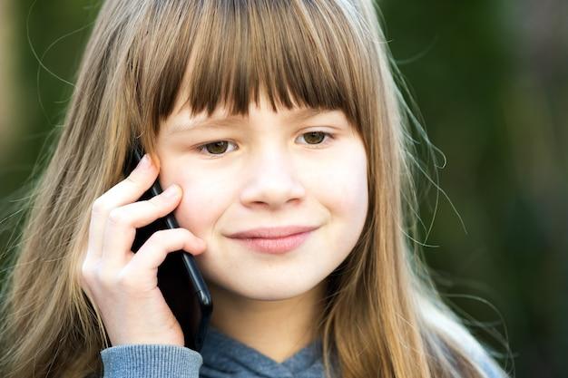 Retrato de menina bonita com cabelo comprido, falando no celular.