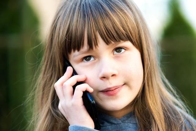 Retrato de menina bonita com cabelo comprido falando no celular