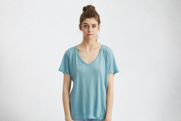 Retrato de menina bonita com coque de cabelo mordendo o lábio, olhando com expressão de arrependimento ou preocupação