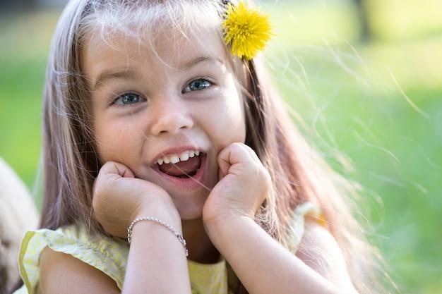 Retrato de menina bonita com expressão de rosto feliz, sorrindo ao ar livre, aproveitando o dia quente de verão ensolarado.