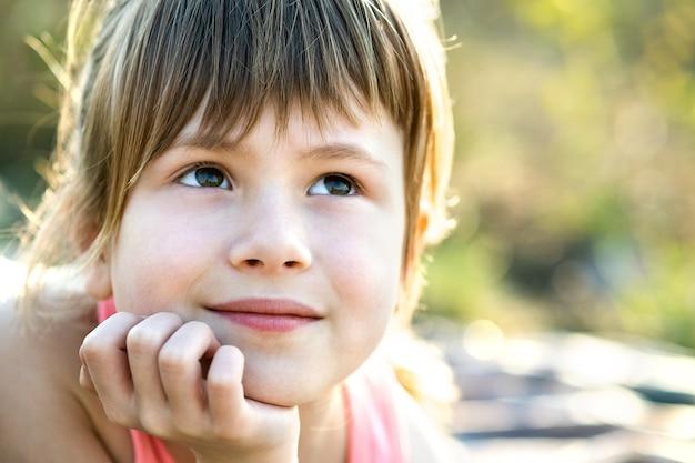Retrato de menina bonita com olhos cinzentos e cabelo longo loiro, apoiando-se nas mãos, sorrindo alegremente ao ar livre no fundo desfocado brilhante. linda criança feminina num dia quente de verão lá fora.
