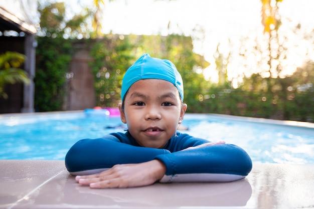 Retrato de menina bonita criança asiática vestindo fato de banho na piscina