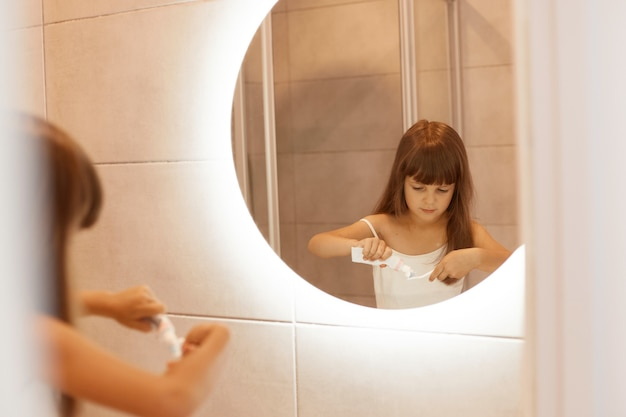 Retrato de menina bonita criança de cabelos escuros escovando os dentes no banheiro, espremendo a pasta de dente de um tubo, em frente ao espelho, vestindo camiseta branca sem mangas.