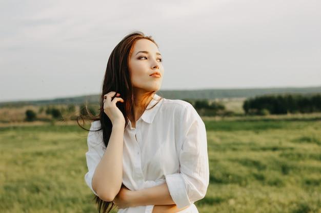Retrato de menina bonita de cabelo comprido despreocupado em roupas brancas no campo ao pôr do sol