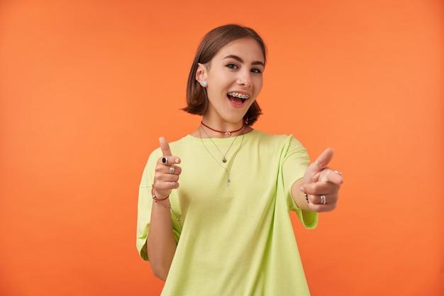 Retrato de menina bonita e alegre, apontando para a câmera e com um sorriso largo. olhando feliz. vestindo camiseta verde, aparelho dentário, pulseiras e anéis. isolado contra parede laranja