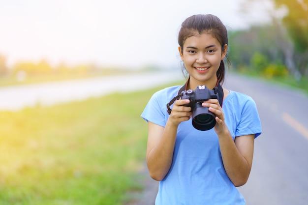 Retrato, de, menina bonita, em, azul, t-shirt, e, calças brim, sorrindo, com, um, câmera, ligado, mãos