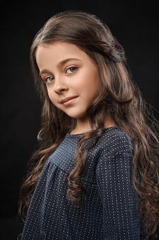 Retrato de menina bonita em estúdio em fundo preto.