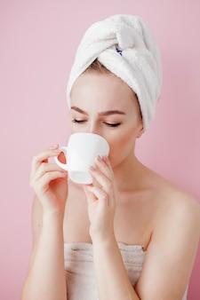 Retrato de menina bonita em roupão com uma xícara de chá, mulher loira de conceito de relaxamento vestindo roupão e toalha na cabeça após o banho.