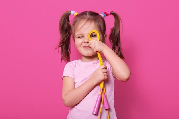 Retrato de menina bonita emocional, usa camiseta rosa com duas caudas de pônei. garoto encantador olha através da corda de pular torcida na câmera. poses de modelo pequeno.