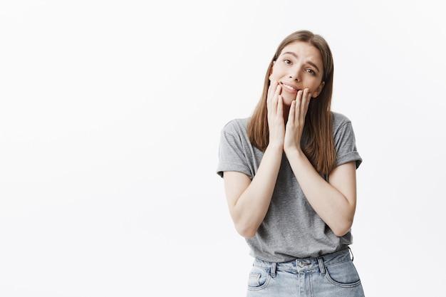 Retrato de menina bonita estudante caucasiano com cabelos escuros e olhos castanhos em camiseta cinza e calça jeans, sorrindo suavemente, com um olhar suave e relaxado, tocando o rosto com os dedos