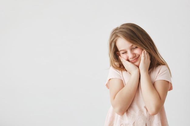Retrato de menina bonita feliz com cabelos loiros na camiseta rosa, apertando o rosto com as mãos, fechando os olhos, sentindo-se tímido depois que o garoto bonito na escola a fez elogiar