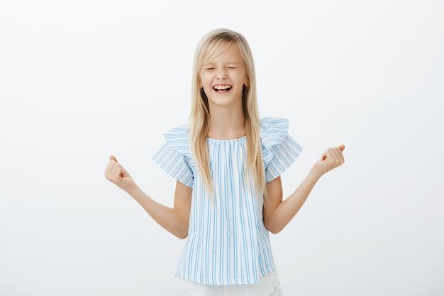 Retrato de menina bonita feliz e animada com cabelos louros e blusa azul, cerrando o punho levantado, fechando os olhos e gritando de alegria e felicidade, sendo alegre, conquistando o primeiro lugar no evento