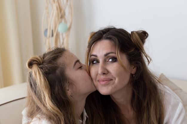 Retrato de menina bonita feliz na sala de estar beijando sua mãe na camisa branca