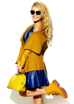 Retrato de menina bonita feliz sorridente mulher loira doce em roupas de camisola de inverno quente casual hipster, com bolsa amarela em óculos de sol