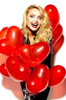 Retrato de menina bonita feliz sorridente mulher loira doce segurando nas mãos balões de coração vermelho em roupas casual preto hipster