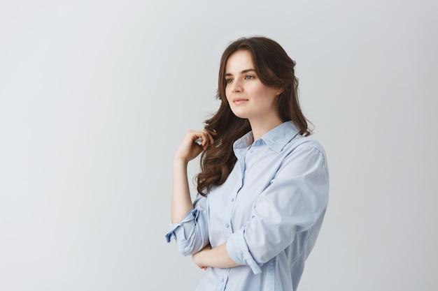 Retrato de menina bonita feminina com cabelo longo ondulado escuro, olhando de lado com expressão relaxada e calma. copie o espaço.