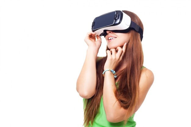 Retrato de menina bonita jovem sorridente feliz obtendo experiência usando óculos vr-fone de ouvido da realidade virtual isolado