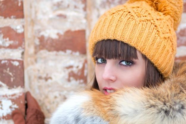 Retrato de menina bonita no chapéu de inverno