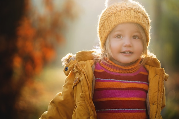 Retrato de menina bonita no chapéu de malha amarela e casaco amarelo