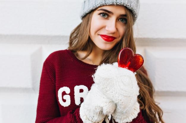 Retrato de menina bonita no suéter marsala e luvas brancas na parede cinza. ela usa chapéu de malha, segura pirulito de coração e está olhando.