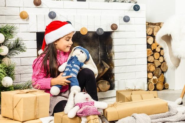 Retrato de menina bonita perto de uma lareira no natal