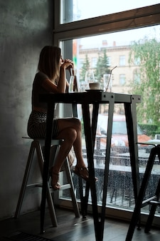 Retrato de menina bonita sentada no bar e olhando para a janela
