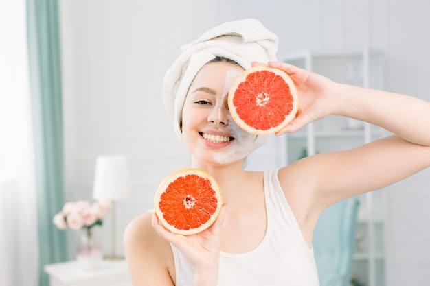 Retrato de menina bonita sorridente com uma toalha branca na cabeça segurando as metades de toranjas perto do rosto, fechando um olho, pele lisa perfeita saudável, máscara branca em uma metade do rosto, sobre o espaço de luz