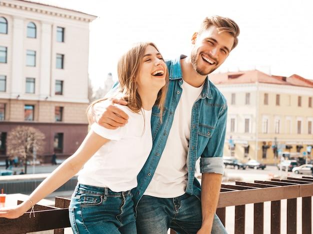 Retrato de menina bonita sorridente e seu namorado bonitão em roupas de verão casual. . abraçando