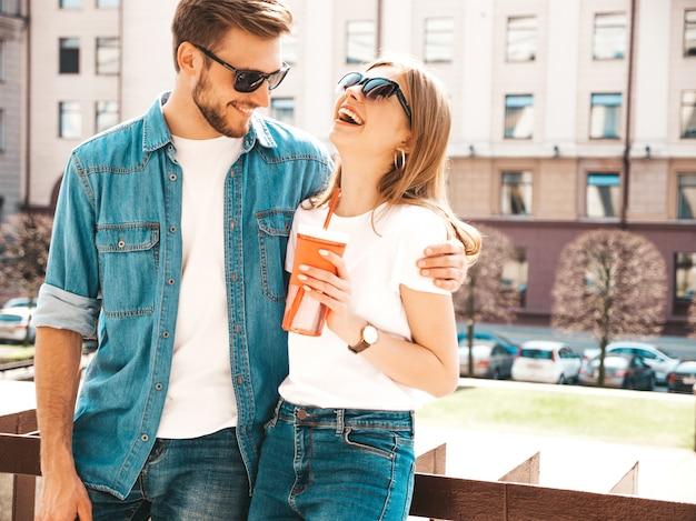 Retrato de menina bonita sorridente e seu namorado bonitão em roupas de verão casual. . com garrafa de água e palha