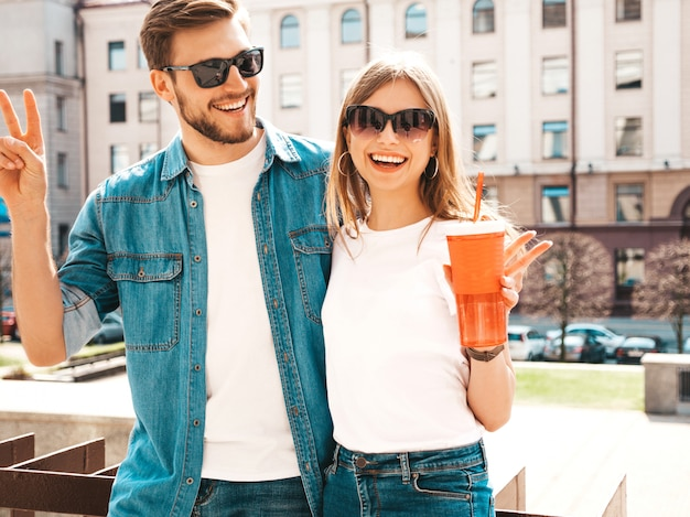Retrato de menina bonita sorridente e seu namorado bonitão em roupas de verão casual. . mulher com garrafa de água e palha