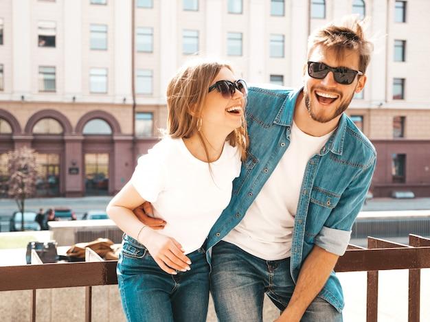 Retrato de menina bonita sorridente e seu namorado bonito em roupas de verão casual e óculos de sol. . abraçando