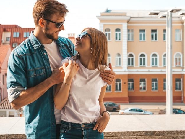 Retrato de menina bonita sorridente e seu namorado bonito em roupas de verão casual e óculos de sol.