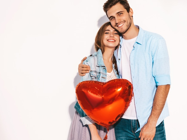Retrato de menina bonita sorridente e seu namorado bonito segurando balões em forma de coração e rindo. casal feliz no amor. feliz dia dos namorados