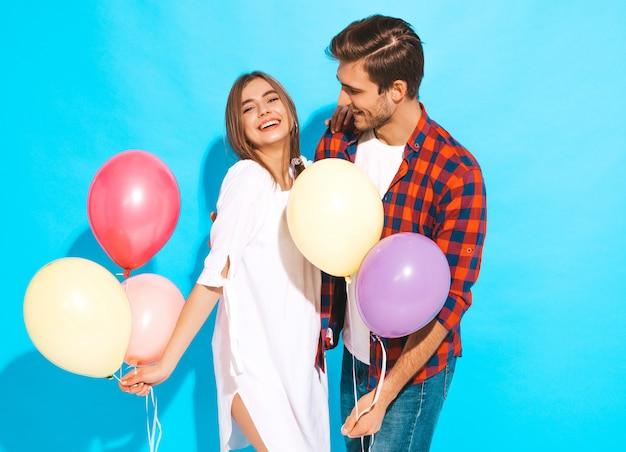 Retrato de menina bonita sorridente e seu namorado bonito segurando o monte de balões coloridos e rindo. feliz aniversário
