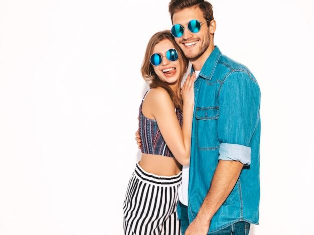 Retrato de menina bonita sorridente e seu namorado considerável rindo. casal alegre feliz em óculos de sol redondos.