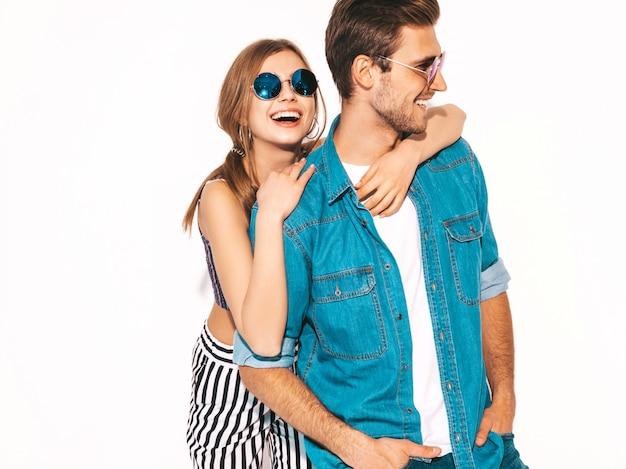 Retrato de menina bonita sorridente e seu namorado considerável rindo. casal alegre feliz em óculos de sol.