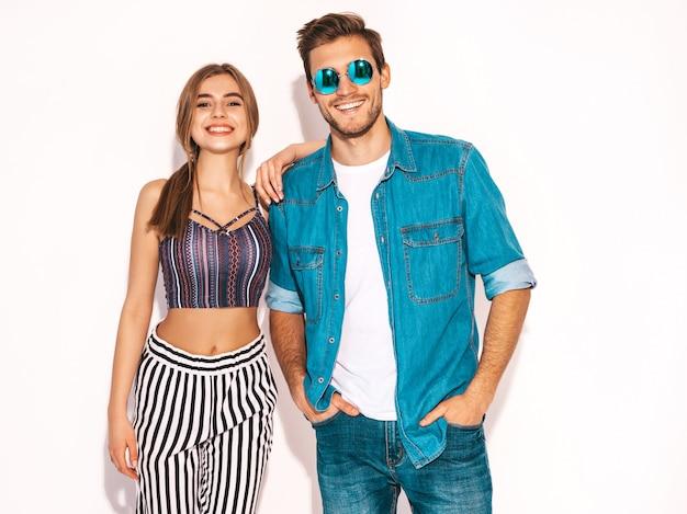 Retrato de menina bonita sorridente e seu namorado considerável rindo. feliz casal alegre em óculos de sol redondos. dia dos namorados. abraçando