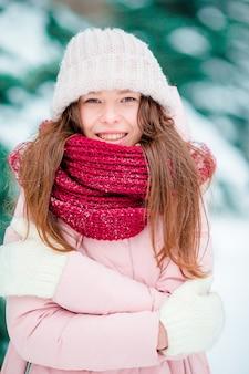 Retrato de menina bonita sorrindo ao ar livre no dia de neve de inverno bonito