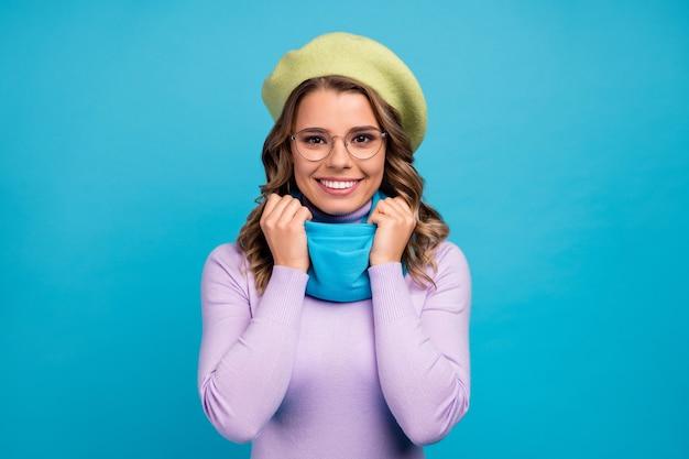 Retrato de menina bonita tocando seu lenço e aproveitando o tempo livre na parede azul