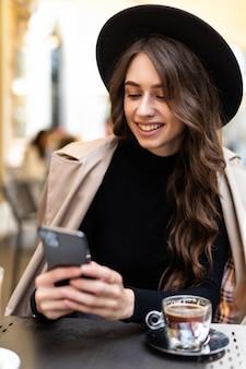 Retrato de menina bonita usar chapéu, usando seu telefone celular no café ao ar livre.