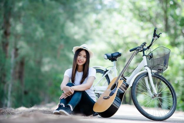 Retrato, de, menina bonita, violão jogo, com, bicicleta, em, natureza