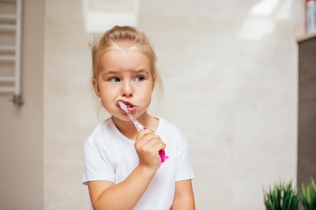 Retrato de menina bonitinha com cabelo loiro que dente de limpeza com escova e creme dental no banheiro. copyspace