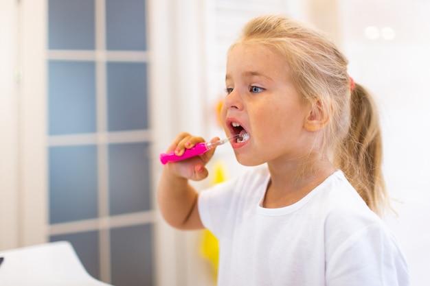 Retrato de menina bonitinha com cabelo loiro que dente de limpeza com escova e creme dental no banheiro.