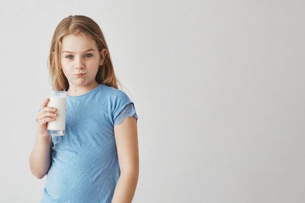 Retrato de menina bonitinha com longos cabelos loiros e olhos azuis com bigode de leite e expressão de rosto engraçado, segurando o copo na mão.
