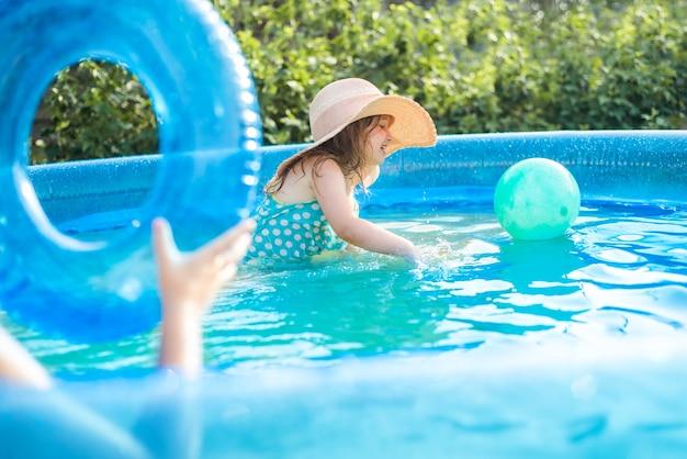 Retrato de menina bonitinha na piscina ao ar livre.