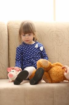 Retrato de menina bonitinha no sofá com piggybank