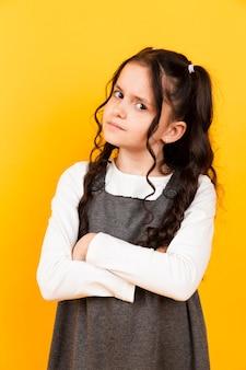 Retrato de menina bonitinha posando em fundo amarelo