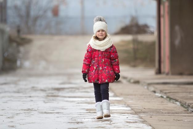 Retrato de menina bonito jovem engraçado bonito em roupas de inverno quente agradável andando com confiança sozinho no fundo de espaço de cópia branco brilhante turva ao ar livre. beleza do conceito de infância.