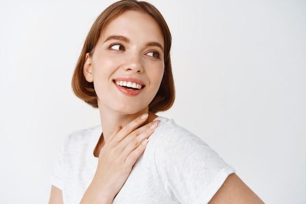 Retrato de menina cândida sorridente com pele limpa fresca, olhando de lado no espaço vazio, tocando o pescoço. mulher olhando com maquiagem de luz natural, parede branca